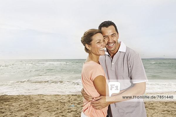 Spain  Mid adult couple on beach at Palma de Mallorca  smiling