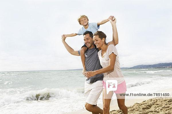 Spanien  Familienspaziergang am Strand von Palma de Mallorca  lachend