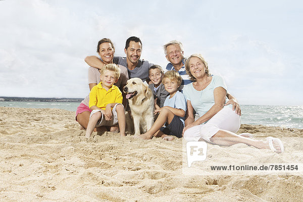 Spain  Portrait of family sitting on beach at Palma de Mallorca  smiling
