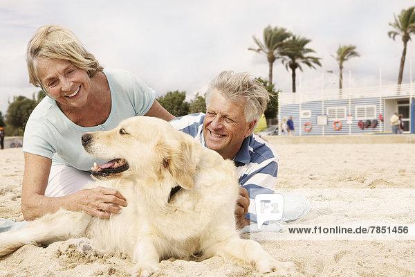 Spanien  Seniorenpaar mit Hund am Strand von Palma de Mallorca  lächelnd