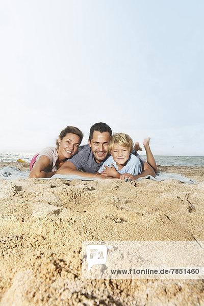 Spanien  Familie am Strand von Palma de Mallorca liegend  lächelnd