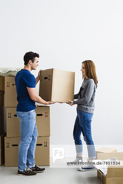 Germany  Munich  Young couple holding cardboard box  smiling