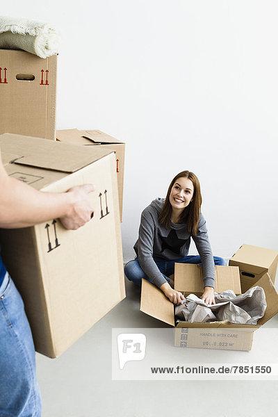 Junger Mann hält Karton  während Frau Karton verpackt