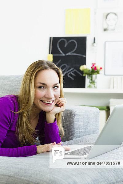 Junge Frau mit Laptop  lächelnd