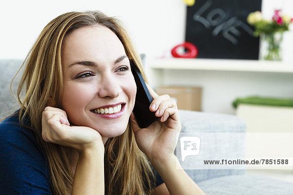 Junge Frau spricht auf dem Handy  lächelnd