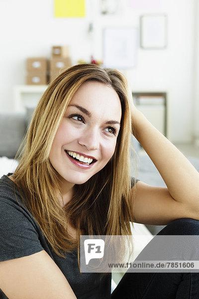 Junge Frau schaut weg  lächelnd