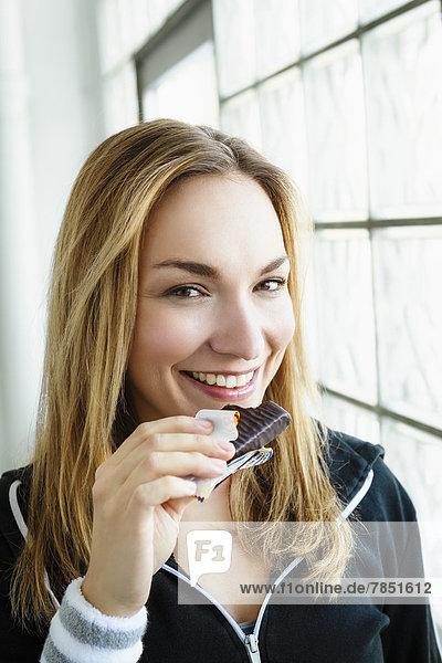 Porträt einer jungen Frau beim Schokoladenessen  lächelnd
