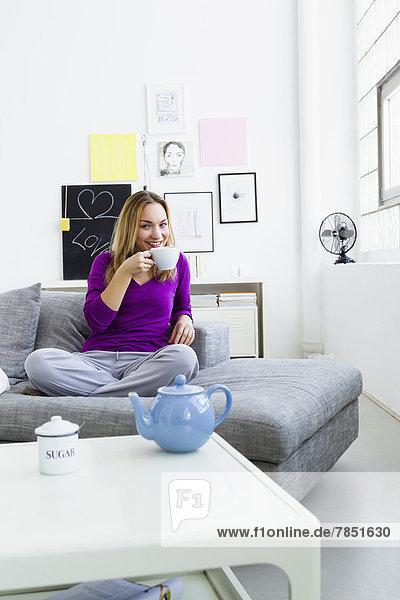 Porträt einer jungen Frau  die Tee trinkt  lächelnd