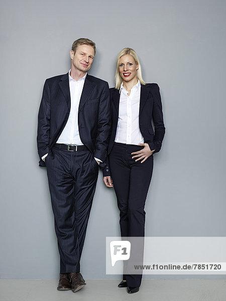 Geschäftspaar vor grauem Hintergrund stehend  lächelnd  Portrait