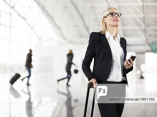 Geschäftsfrau mit Aktentasche und Handy  lächelnd