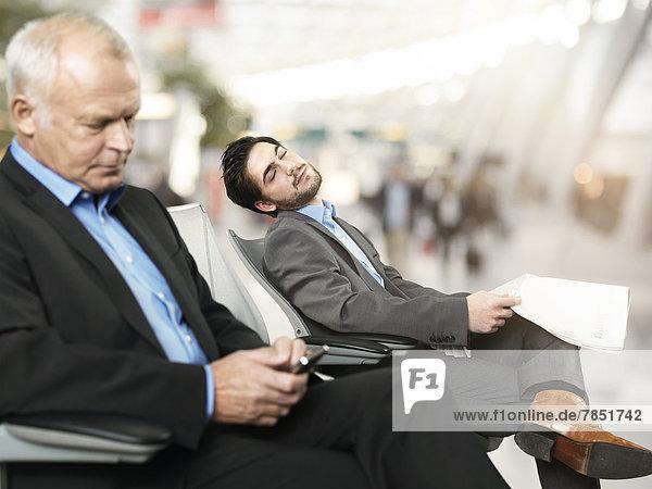 Älterer Mann  der das Handy benutzt  während der mittlere erwachsene Mann im Hintergrund schläft.