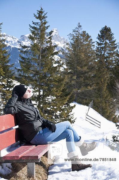 Österreich  Frau entspannt auf der Bank in den Tannheimer Alpen