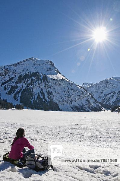Österreich  Frau sitzend im Schnee in den Tannheimer Alpen