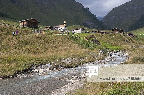 Italien  Blick auf die Pfunderer Berge und das Bergdorf mit Wanderern in Bachnähe