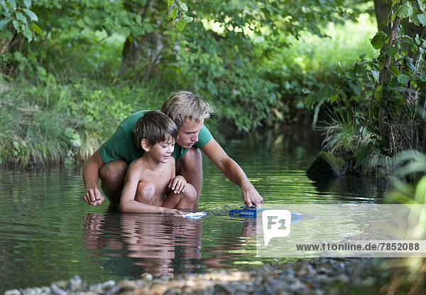 Austria  Friends playing with boat in stream  smiling