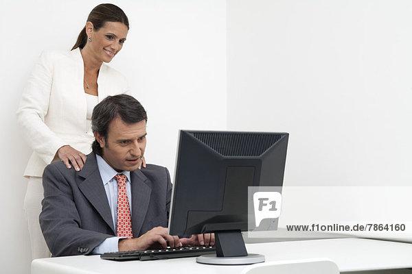 Geschäftsfrau gibt Geschäftsmann Massage bei der Arbeit