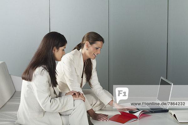 Geschäftsfrauen lesen gemeinsam Magazin