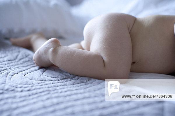 Nacktes Baby auf dem Bett liegend  abgeschnitten
