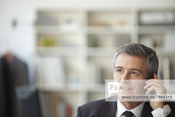 Der reife Geschäftsmann im Gespräch mit dem Handy