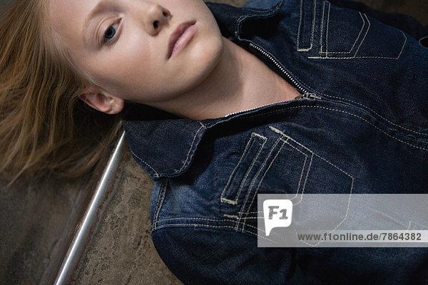 Junge Frau auf dem Boden liegend  Porträt