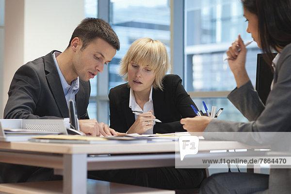 Geschäftsleute  die den Vertrag überprüfen  während sie sich mit weiblichen Führungskräften treffen.
