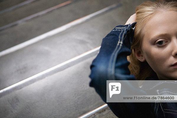 Junge Frau auf der Treppe liegend mit Händen hinter dem Kopf  Portrait