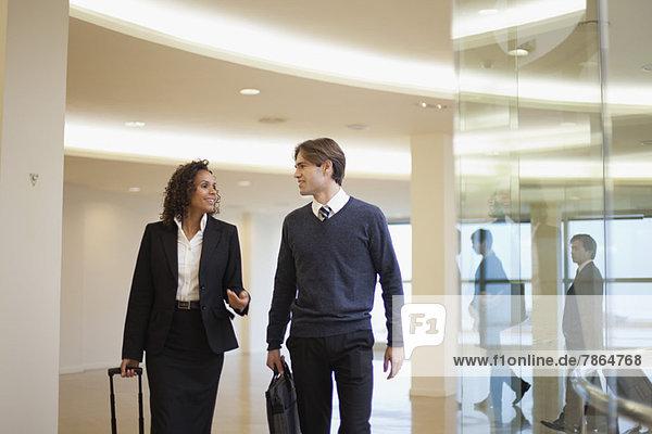 Geschäftsfreunde gehen und reden gemeinsam im Flur