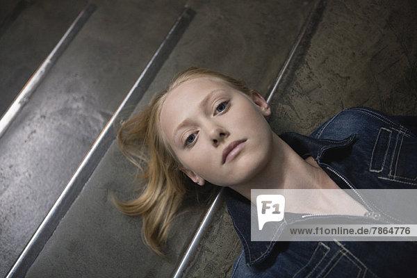 Junge Frau auf der Treppe liegend  Porträt