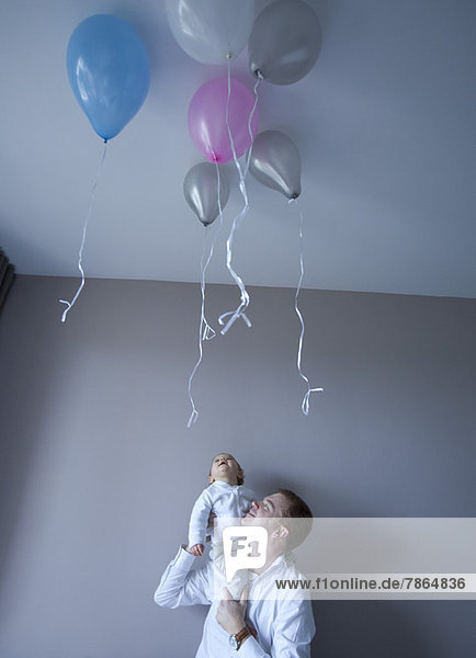 Vater trägt Baby auf der Schulter  Baby blickt auf schwebende Luftballons