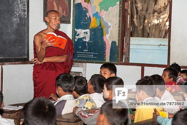 Buddhist monk teaching children  Mahagandhayon Monastic Institution  Amarapura  Mandalay  Myanmar  (Burma).
