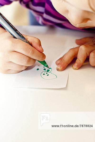 Mädchen malt auf einem Blatt Papier