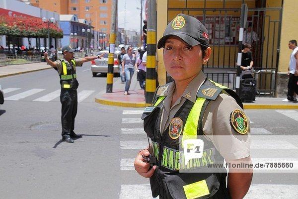 Städtisches Motiv  Städtische Motive  Straßenszene  Straßenszene  überqueren  Frau  Mann  Sicherheit  Hispanier  Polizei  Strafverfolgung  lockend  gestikulieren  Schutzkleidung  Peru  Straßenverkehr  Trillerpfeife  Pfeife