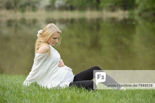 Junge schwangere Frau sitzt auf einer Wiese