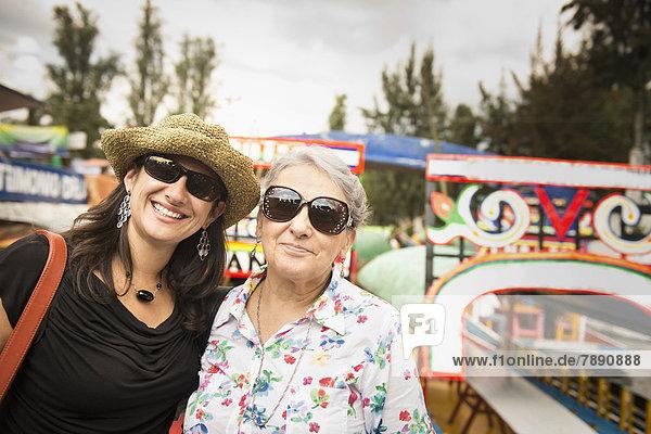 Hispanic women smiling at amusement park