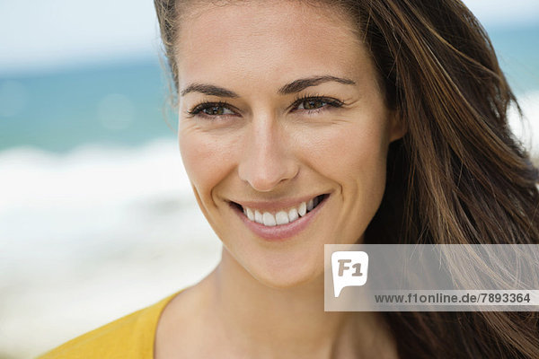 Close-up of a woman smiling on the beach