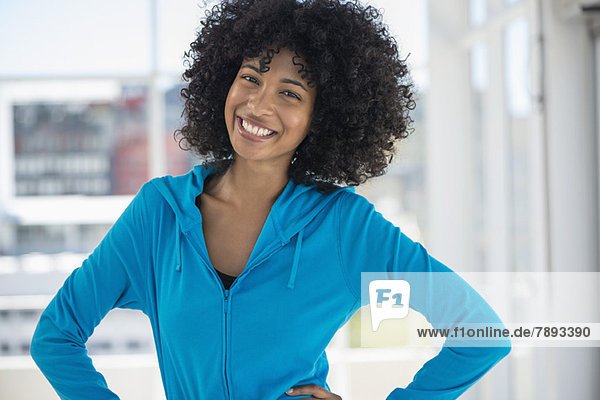 Portrait of a smiling woman standing with hands on hips