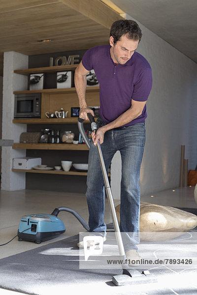 Mann Reinigung Wohnzimmer mit Staubsauger