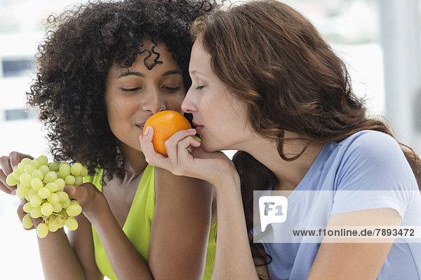 Nahaufnahme von zwei Freundinnen  die Früchte riechen