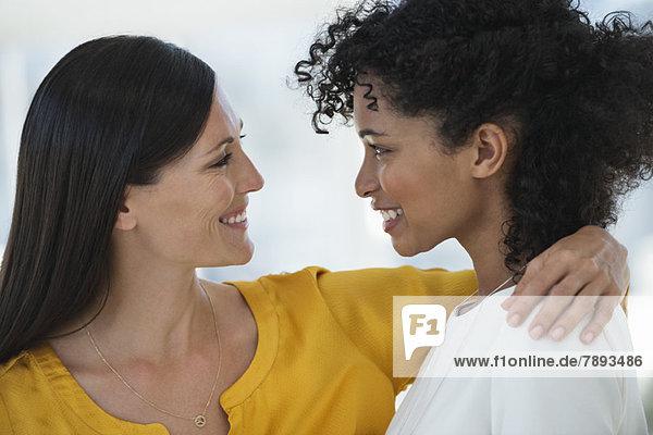 Nahaufnahme von zwei sich anlächelnden Freundinnen