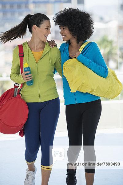 Zwei glückliche Freundinnen mit Sporttaschen