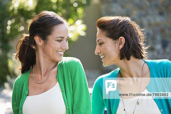 Zwei Freundinnen lächeln zusammen