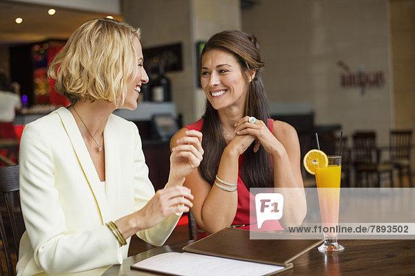 Zwei Freundinnen  die sich in einem Restaurant anlächeln.