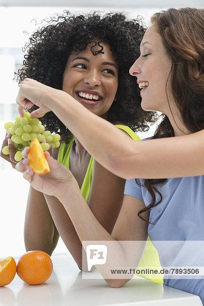Nahaufnahme von zwei lächelnden Freundinnen beim Obstessen