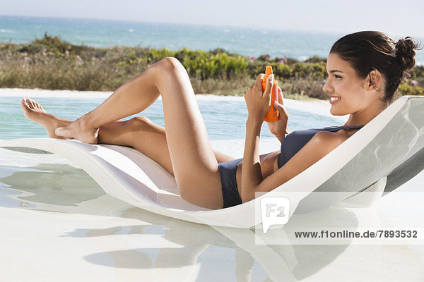 Schöne Frau beim Sonnenbaden am Strand mit Sonnencreme