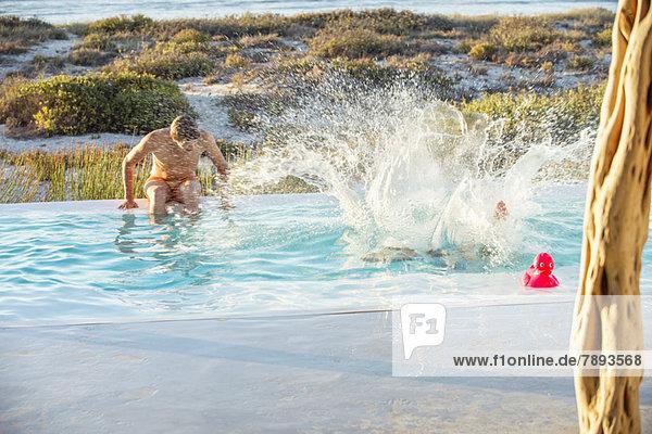 Zwei männliche Freunde genießen in einem Swimmingpool am Strand