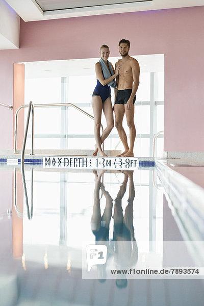 Paar am Pool stehend Paar am Pool stehend