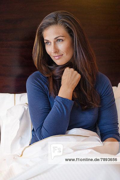 Frau im Hotelzimmer auf dem Bett sitzend