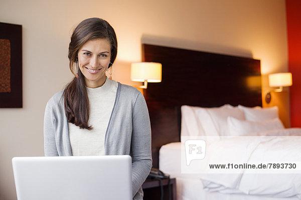 Frau benutzt einen Laptop in einem Hotelzimmer und lächelt