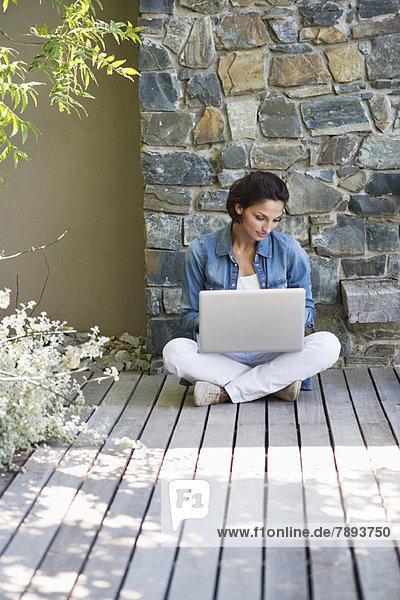 Frau  die auf einem Hartholzboden sitzt und einen Laptop benutzt.
