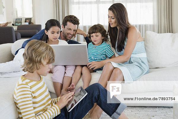 Junge  der ein digitales Tablett benutzt  während seine Familie auf einen Laptop schaut.